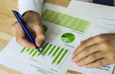 Businessman analyzing sustainable development opportunities charts at workspace. Hand holding a pen and green charts.